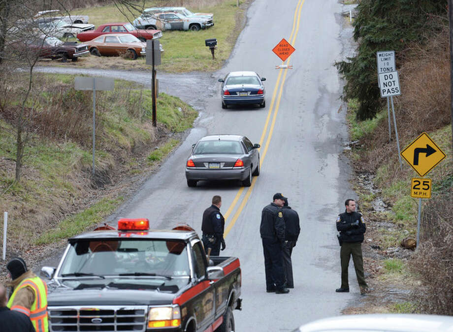 Local law enforcement block off road along Rt. 22 near the Canoe Creek State Park, Pa. while investigating a shooting on Friday, Dec. 21, 2012. The suspect fired at troopers responding to Friday morning's shootings in Frankstown Township, about 70 miles west of Harrisburg. The fleeing gunman then crashed head-on into a trooper's car and got out of his truck and shot again at police, who returned fire and killed him. Blair County District Rich Consiglio says the gunman killed two men and one woman. (AP Photo/Altoona Mirror, J.D. Cavrich) / Altoona Mirror