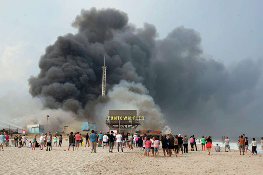 Onlookers watch from the shore as black smoke rises from a fire on the Seaside Heights, N.J. boardwalk Thursday, Sept. 12, 2013. The fire started in the vicinity of an ice cream shop and burned several blocks of boardwalk and businesses in a town that was still rebuilding from damage caused by Superstorm Sandy. (AP Photo/The Asbury Park Press, Bob Bielk) NO SALES / The Asbury Park Press