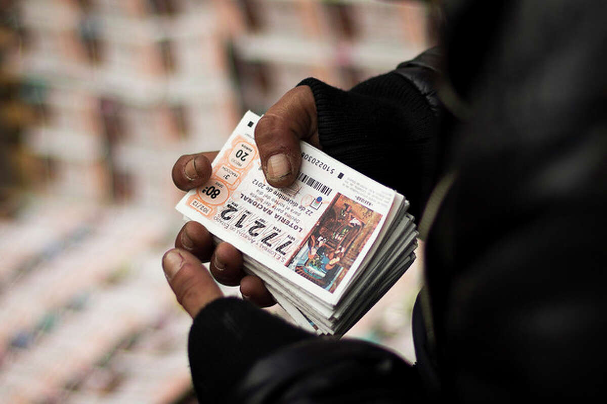 """A seller holds a pack of tickets for the cash-strapped country's famed Christmas lottery, in Madrid, Friday, Dec. 21, 2012. Many players say they're hoping to win so they can pay off debt or help relatives facing heavy economic burdens. Known as """"El Gordo"""" (The Fat One) and billed as the world's richest lottery, the drawing will hand out about 2.5 billion of euro ($3.3 billion) on Saturday. The top prize is about 400,000 euro ($530,000) but there are expected to be hundreds or thousands of tickets awarded for that amount. (AP Photo/Daniel Ochoa de Olza)"""