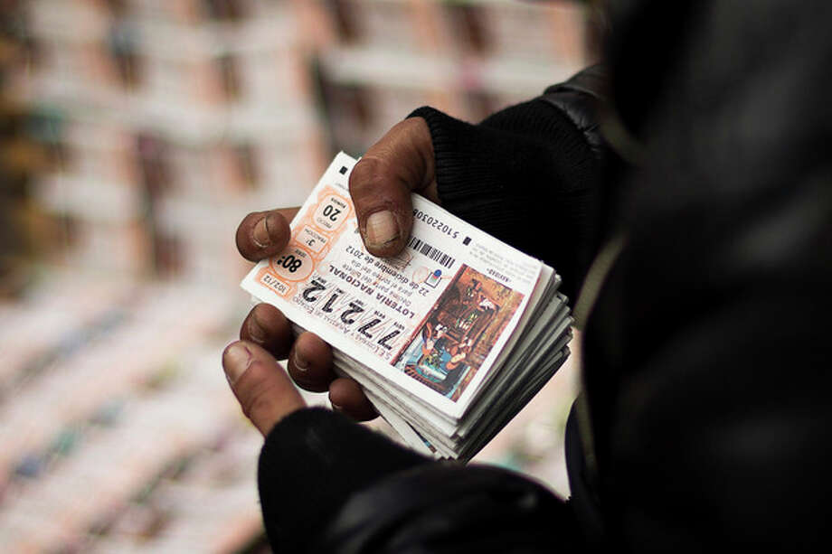 "A seller holds a pack of tickets for the cash-strapped country's famed Christmas lottery, in Madrid, Friday, Dec. 21, 2012. Many players say they're hoping to win so they can pay off debt or help relatives facing heavy economic burdens. Known as ""El Gordo"" (The Fat One) and billed as the world's richest lottery, the drawing will hand out about 2.5 billion of euro ($3.3 billion) on Saturday. The top prize is about 400,000 euro ($530,000) but there are expected to be hundreds or thousands of tickets awarded for that amount. (AP Photo/Daniel Ochoa de Olza) / AP"