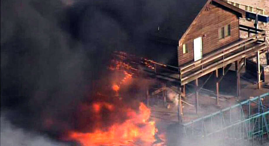 CORRECTS LOCATION TO SEASIDE HEIGHTS INSTEAD OF SEASIDE PARK - In this image taken from video and provided by Fox 29, flames engulf a building on the boardwalk in the resort community of Seaside Heights, N.J., Thursday, Sept. 12, 2013. The massive fire burned several blocks of boardwalk and businesses along the popular stretch of boardwalk, which was damaged by Superstorm Sandy and was being repaired. (AP Photo/Fox 29) NO SALES / FOX 29