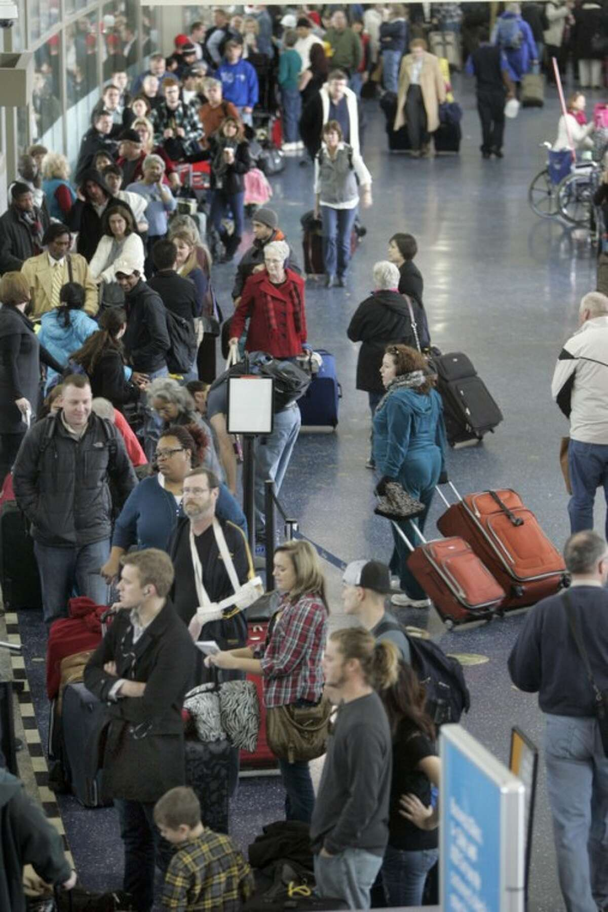 Travelers wait in line at the Southwest Airlines ticket counter at Kansas City International Airport on Thursday, Dec. 20 2012, in Kansas City, Mo. Many flights were canceled due to inclement weather. (AP Photo/The Kansas City Star, David Pulliam)