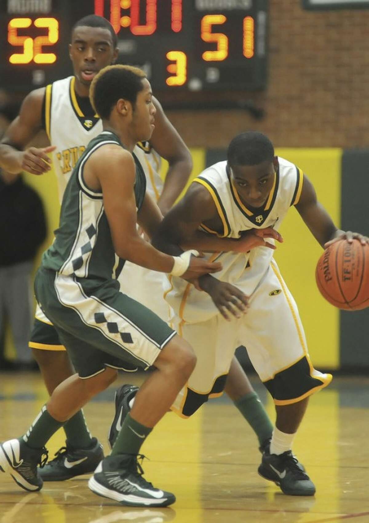 Hour photo/John Nash Schadrac Casimir of Trinity Catholic, right, protects the ball as he dribbles past Norwalk's Jeremy Linton while Brandon Wheeler looks on. Trinity turned back visiting Norwalk, 77-67, in Friday night's clash of early-season unbeatens at Walsh Gymnasium in Stamford.
