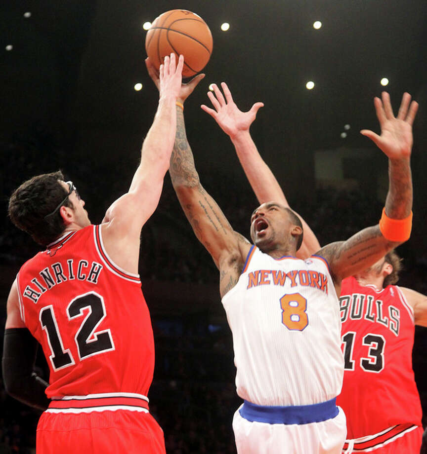 New York Knicks' J.R. Smith (8) goes to the the basket against Chicago Bulls' Kirk Hinrich (12) and Joakim Noah during the first half of an NBA basketball game on Friday, Dec. 21, 2012, at Madison Square Garden in New York. (AP Photo/Mary Altaffer) / AP