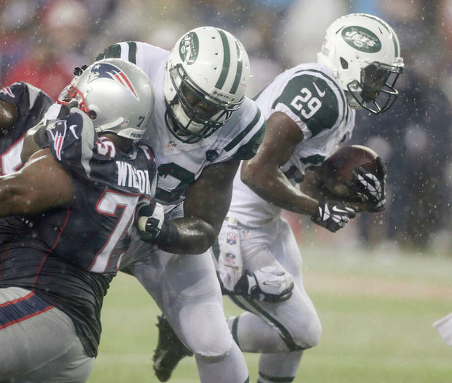 New York Jets running back Bilal Powell (29) runs past New England Patriots defensive tackle Vince Wilfork (75) during the third quarter of an NFL football game Thursday, Sept. 12, 2013, in Foxborough, Mass. (AP Photo/Charles Krupa) / AP