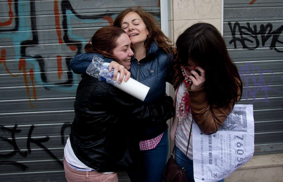 "Carmen, centre hugs her daughter Azahara, right, and an unidentified cousin after winning the main Christmas lottery prize ""El Gordo"" (""The Fat One"") in Alcala de Henares, just outside of Madrid, Saturday Dec. 22, 2012. Lucky winners of Spain's cherished Christmas lottery, the world's richest, celebrated Saturday, as initial indicators show more than a dozen locations where lucky tickets were sold, each picking up the maximum prize of euro 400,000 (US dlrs 529,840), and some thousands of tickets yielding smaller prizes. (AP Photo/Paul White) / AP"