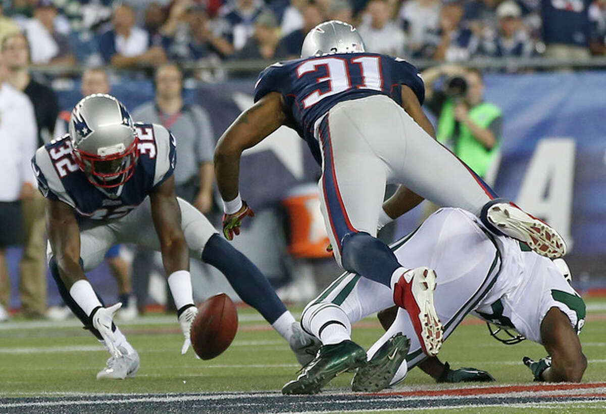 New England Patriots free safety Devin McCourty (32) scoops up a fumble by New York Jets wide receiver Stephen Hill, right, after he was knocked to the ground by Patriots cornerback Aqib Talib (31) in the first quarter of an NFL football game Thursday, Sept. 12, 2013, in Foxborough, Mass. (AP Photo/Elise Amendola)