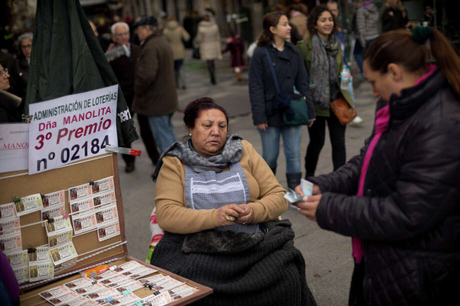"A woman buy tickets for the cash-strapped country's famed Christmas lottery, in Madrid, Friday, Dec. 21, 2012. Many players say they're hoping to win so they can pay off debt or help relatives facing heavy economic burdens. Known as ""El Gordo"" (The Fat One) and billed as the world's richest lottery, the drawing will hand out about 2.5 billion of euro ($3.3 billion) on Saturday. The top prize is about 400,000 euro ($530,000) but there are expected to be hundreds or thousands of tickets awarded for that amount. (AP Photo/Daniel Ochoa de Olza) / AP"