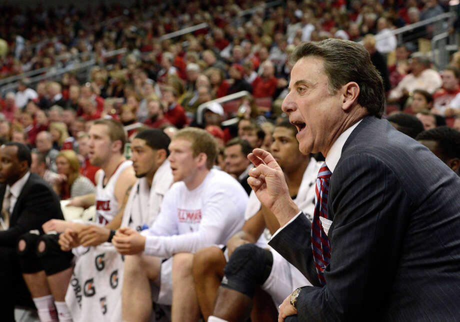 Louisville head coach Rick Pitino, right, shouts instructions to his team during the first half of an NCAA college basketball game against Florida on Wednesday, Dec. 19, 2012, in Louisville, Ky. (AP Photo/Timothy D. Easley) / FR43398 AP