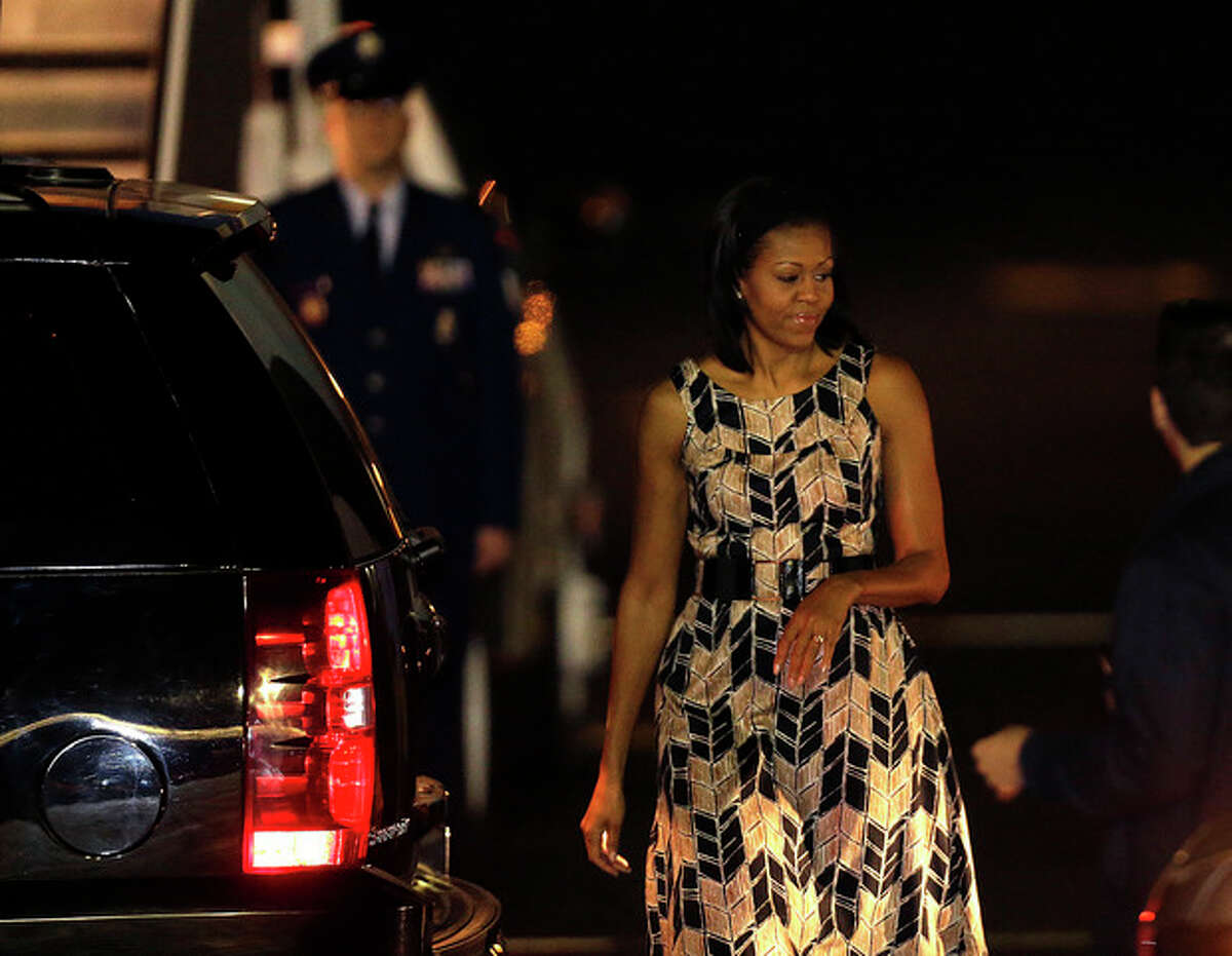 First lady Michelle Obama walks to the presidential limo after arriving with President Barack Obama and their daughters, not pictured, at Honolulu Joint Base Pearl Harbor-Hickam in Honolulu, for the start of their holiday vacation, Saturday, Dec. 22, 2012. (AP Photo/Gerald Herbert)