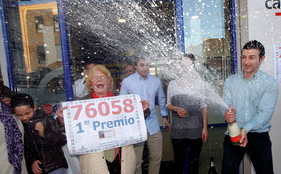 Workers and friends of a lottery office celebrate. after selling a ticket with the number 76058 corresponding to the Jackpot worth euro 4 million or euro 400,000 for each tenth of the ticket, during the Spanish National Lottery draw, in Manises, Valencia, eastern Spain, Saturday Dec. 22, 2012 After a brutal year of economic hardship that deepened with unemployment hitting 25 percent, Spaniards across the country Saturday were hoping for relief from payouts by the nation's famed Christmas lottery _ the world's richest, with €2.5 billion ($3.3 billion) in tax-free awards. (AP Photo/Alberto Saiz) / AP
