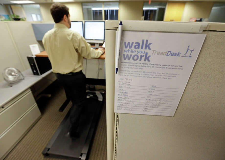 Josh Baldonado, an administrative assistant at Brown & Brown Insurance, works at a treadmill desk in the firms offices in Carmel, Ind., Wednesday, Aug. 28, 2013. Workers sign up for 30 slots not he treadmills and have their phone and computer transferred to the workstations. Being glued to your desk is no longer an excuse for not having time to exercise as a growing number of Americans are standing, walking and even cycling their way through the work day at treadmill desks, standup desks or other moving work stations. (AP Photo/Michael Conroy) / AP