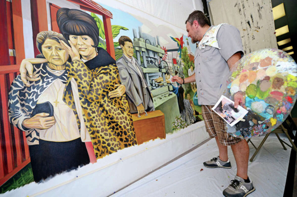 Hour photo / Erik Trautmann Artist Duvian Montoya works on his painting, Norwalk Migration, at the Pop City storefront on Wall St Saturday. Montoya's new work will be exhibited in the Norwalk Public Library's main branch at the end of September.