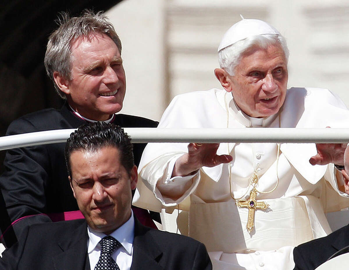 FILE - In this file photo taken Wednesday, May 2, 2012, Pope Benedict XVI, right, arrives in St. Peter's square at the Vatican for a general audience as his then-butler Paolo Gabriele, bottom, and his personal secretary Georg Gaenswein sit in the car with him. The Vatican has summoned journalists for a briefing on Saturday Dec. 22, 2012, for what Italian media report is expected to be the announcement of a pardon for the former butler, Gabiele, who was convicted in October 2012 of aggravated theft after steeling the pontiff's personal papers and leaking them to the media in a bid to expose the