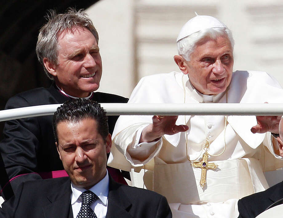 "FILE - In this file photo taken Wednesday, May 2, 2012, Pope Benedict XVI, right, arrives in St. Peter's square at the Vatican for a general audience as his then-butler Paolo Gabriele, bottom, and his personal secretary Georg Gaenswein sit in the car with him. The Vatican has summoned journalists for a briefing on Saturday Dec. 22, 2012, for what Italian media report is expected to be the announcement of a pardon for the former butler, Gabiele, who was convicted in October 2012 of aggravated theft after steeling the pontiff's personal papers and leaking them to the media in a bid to expose the ""evil and corruption"" in the Catholic Church. (AP Photo/Alessandra Tarantino, File) / AP"