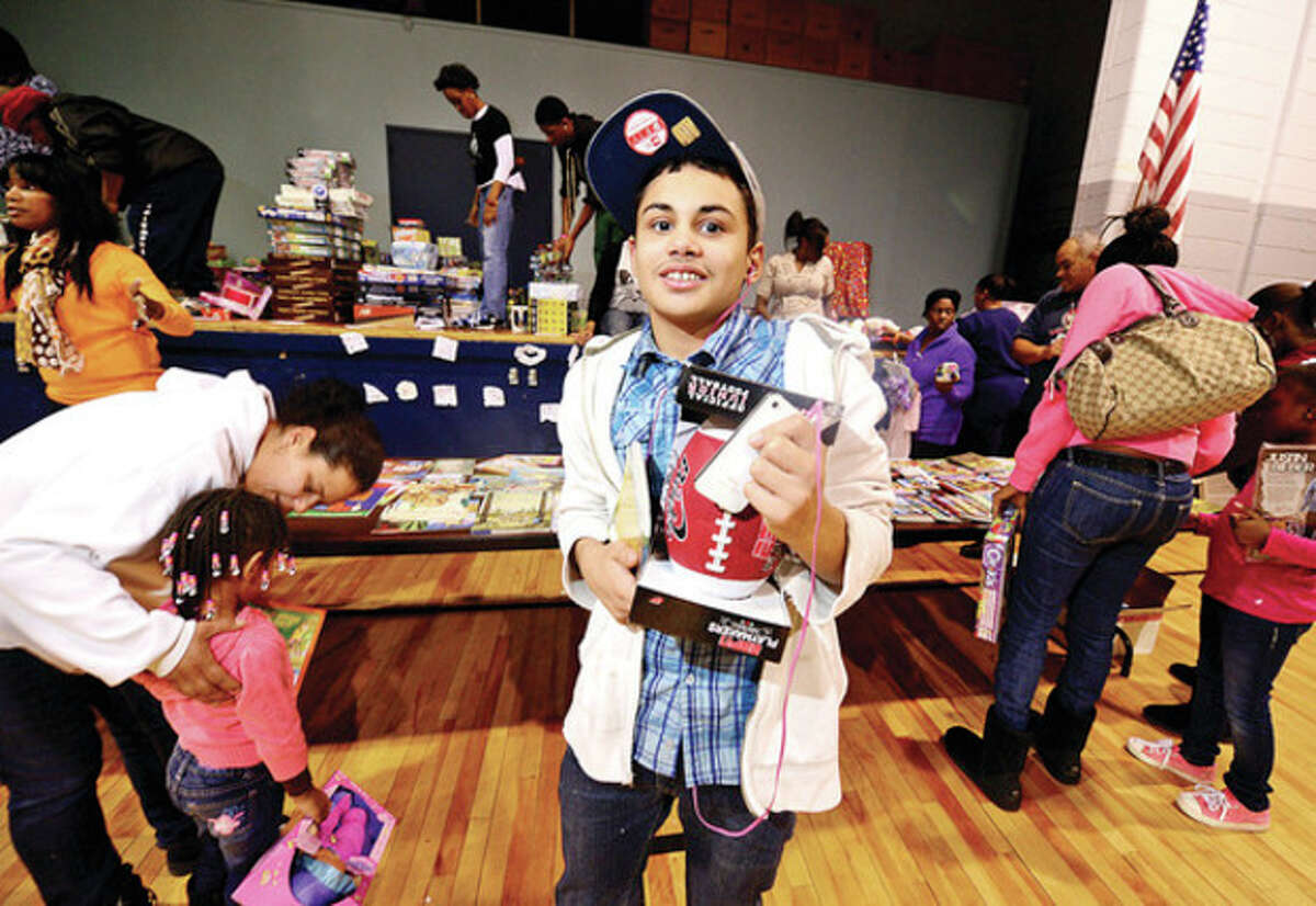 Luis Gonzalez, 13, receives a gift at the Roodner Court Christmas Party at Nathaniel Ely School Saturday. Hour photo / Erik Trautmann