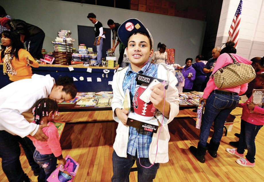 Luis Gonzalez, 13, receives a gift at the Roodner Court Christmas Party at Nathaniel Ely School Saturday.Hour photo / Erik Trautmann / (C)2012, The Hour Newspapers, all rights reserved