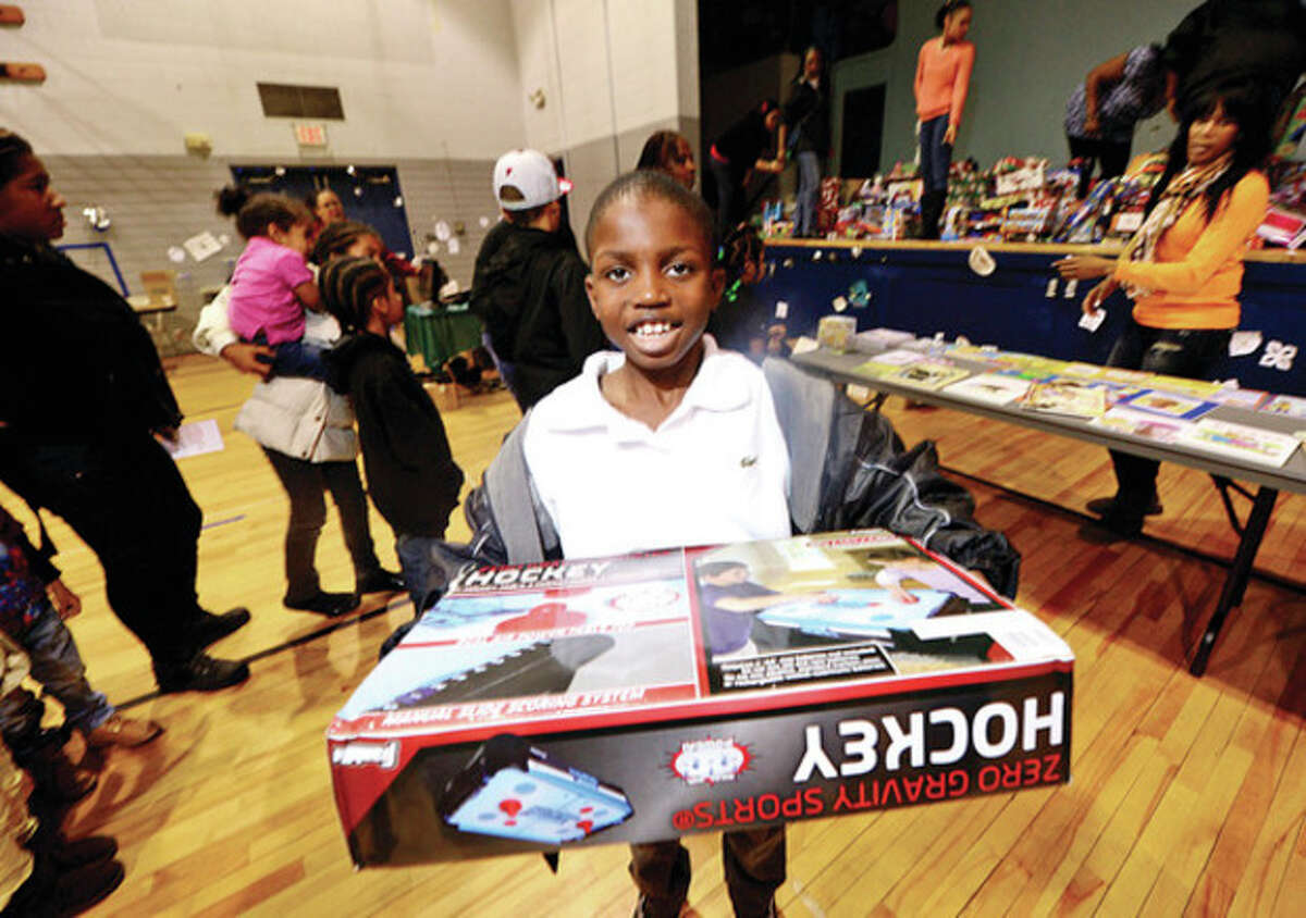 Jahsai Martinfish, 9, receives a gift at the Roodner Court Christmas Party at Nathaniel Ely School Saturday. Hour photo / Erik Trautmann