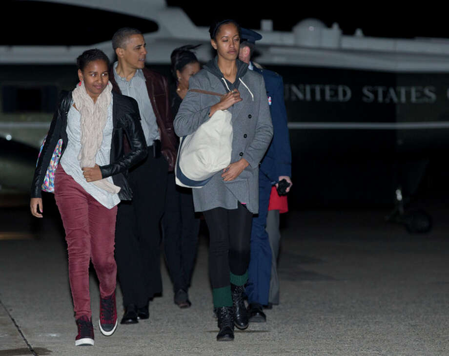 President Barack Obama, First Lady Michelle Obama and their daughters Malia and Sasha walk from Marine One to board Air Force One, Friday, Dec. 21, 2012, in Andrews Air Force Base, Md., en route to a holiday vacation in Honolulu. (AP Photo/Carolyn Kaster) / AP