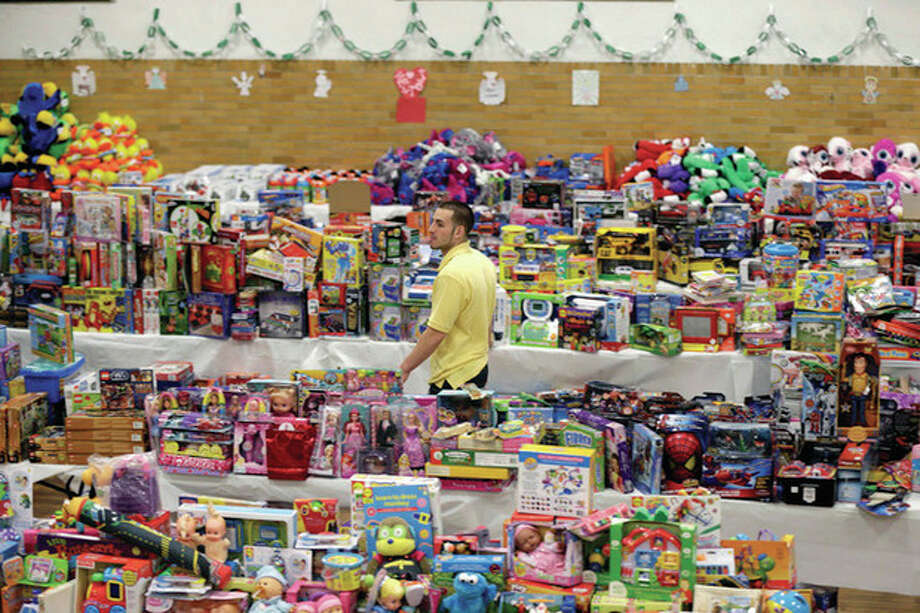 AP photo / Seth WenigVolunteer Anthony Vessicchio of East Haven helps to sort tables full of donated toys at the town hall in Newtown Friday. / AP