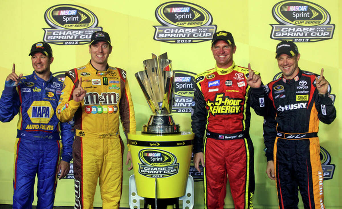 FILE - In this Sept. 7, 2013 file photo, NASCAR Chase drivers celebrate making the Chase after the NASCAR Sprint Cup Series auto race at Richmond International Raceway in Richmond, Va. . From left are Martin Truex, Jr., Kyle Busch, Clint Bowyer and Matt Kenseth. NASCAR's investigation into Bowyer's spin at Richmond ultimately uncovered a series of deliberate actions by Michael Waltrip Racing to alter the race results and the field for the Chase for the Sprint Cup championship. The sordid saga concluded Monday, Sept. 10, 2013, with a hefty penalty that saw Ryan Newman replace Martin Truex Jr. in the Chase as MWR was fined $300,000, and general manager Ty Norris received an indefinite suspension. (AP Photo/Zach Gibson, File)