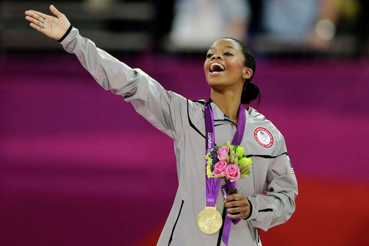FILE - In this Aug. 2, 2012, file photo, Gabrielle Douglas, of the United States, acknowledges the crowd after receiving her gold medal in the artistic gymnastics women's individual all-around competition at the 2012 Summer Olympics in London. Douglas, who became the first African-American gymnast to claim gymnastics?' biggest prize _ the all-around Olympic title _ is The Associated Press?' 2012 female athlete of the year. (AP Photo/Gregory Bull, File)