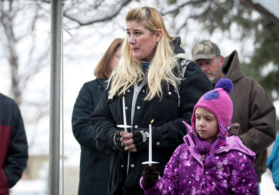 Alicia Caldwell holds her daughter Maggie Boren, both originally from Newtown, Conn., during the community dedication of a grove of trees at the Salt Lake City cemetery in remembrance of victims of the Sandy Hook Elementary shootings, Thursday, Dec. 27, 2012. (AP Photo/The Deseret News, Ben Brewer) SALT LAKE TRIBUNE OUT; PROVO DAILY HERALD OUT; MAGS OUT; MANDATORY CREDIT / The Deseret News