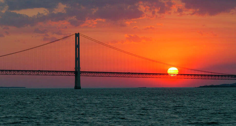 FILE - In this May 31, 2002 file photo, the sun sets over the Mackinac Bridge and the Mackinac Straits as seen from Lake Huron. The bridge is the dividing line between Lake Michigan to the west and Lake Huron to the east. Republicans in the eight-state Great Lake region are matching Democrats' enthusiasm for an array of federal programs benefiting the inland seas, from dredging harbors to controlling invasive predators like the fish-killing sea lamprey. Thirty-eight members of Congress have signed a letter requesting $300 million for 2014. (AP Photo/Al Goldis, File) / AP