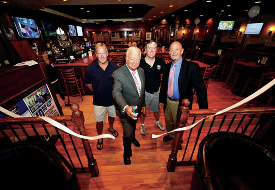 Mayor Richard Moccia, center, cuts the ribbon for the new Brennan's Pub on CT Ave as Gaynor Brennan, Barry Brennan and Mac Mackenzie look on Thursday.Hour photo / Erik Trautmann / (C)2013, The Hour Newspapers, all rights reserved