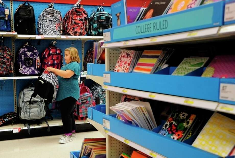 FILE - In this Friday, Aug. 2, 2013, file photo, Raegan Jackson, 10, picks out a backpack shopping at Target in Lynchburg, Va. The government reports on sales at U.S. retailers in August on Friday, Sept. 13, 2013. (AP Photo/News & Daily Advance, Sam O'Keefe) / News & Daily Advance