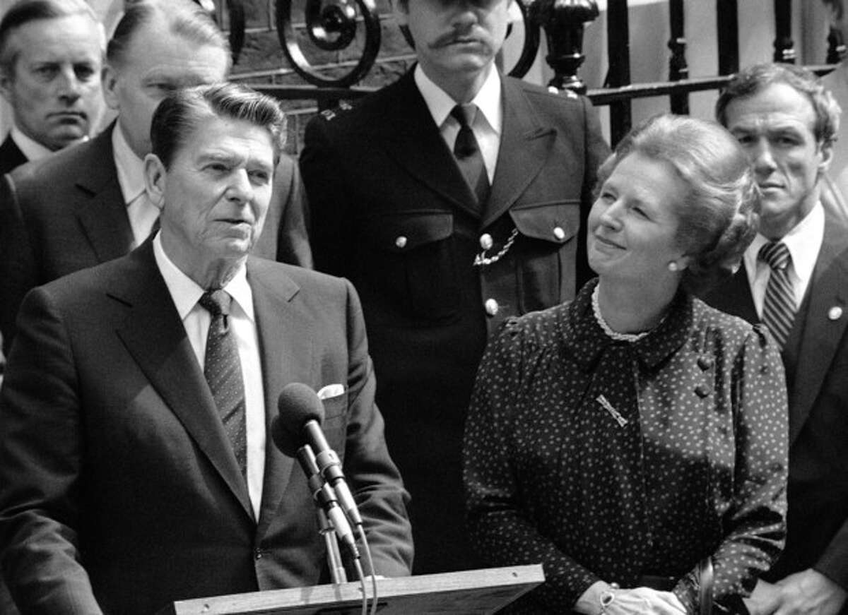 FILE - In this June 9, 1982 file photo, Britain's Prime Minister Margaret Thatcher, right, smiles with satisfaction as President Ronald Reagan makes a farewell speech outside her Downing Street office in London prior to his departure for Bonn. It is not often that the president of the United States needs to seek fashion advice. But when Ronald Reagan was getting ready for a visit to England as a guest of Queen Elizabeth II in June 1982, his people had an important question for the Brits: Just what does one wear to go riding with the queen in the magnificent horse country surrounding Windsor Castle? The answer: Something smart, but casual, of course. Riding boots, breeches and a turtleneck sweater would do fine _ no need for formal riding attire. The fashion inquiry is but one tidbit contained in nearly 500 pages of formerly Confidential documents relating to the Reagan visit being made public Friday, Dec. 28, 2012 by Britain?'s National Archives. (AP Photo/Bob Dear, File)