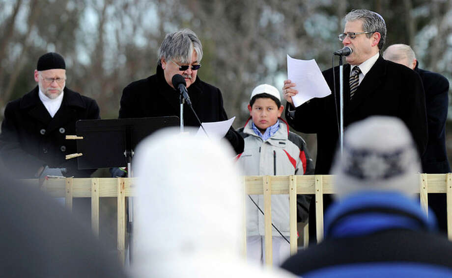 Rev. Mel Kawakami, center, of the Newtown United Methodist Church, and Rabbi Shaul Praver, right, of Congregation Adath Israel in Newtown, speak at an interfaith prayer vigil to remember the victims of the Sandy Hook elementary school shootings Friday, Dec. 28, 2012 in Newtown, Conn. Friday morning marked two weeks since a gunman killed 20 children and six educators at the Sandy Hook Elementary School. (AP Photo/Danbury News-Times, Carol Kaliff) / Danbury News-Times