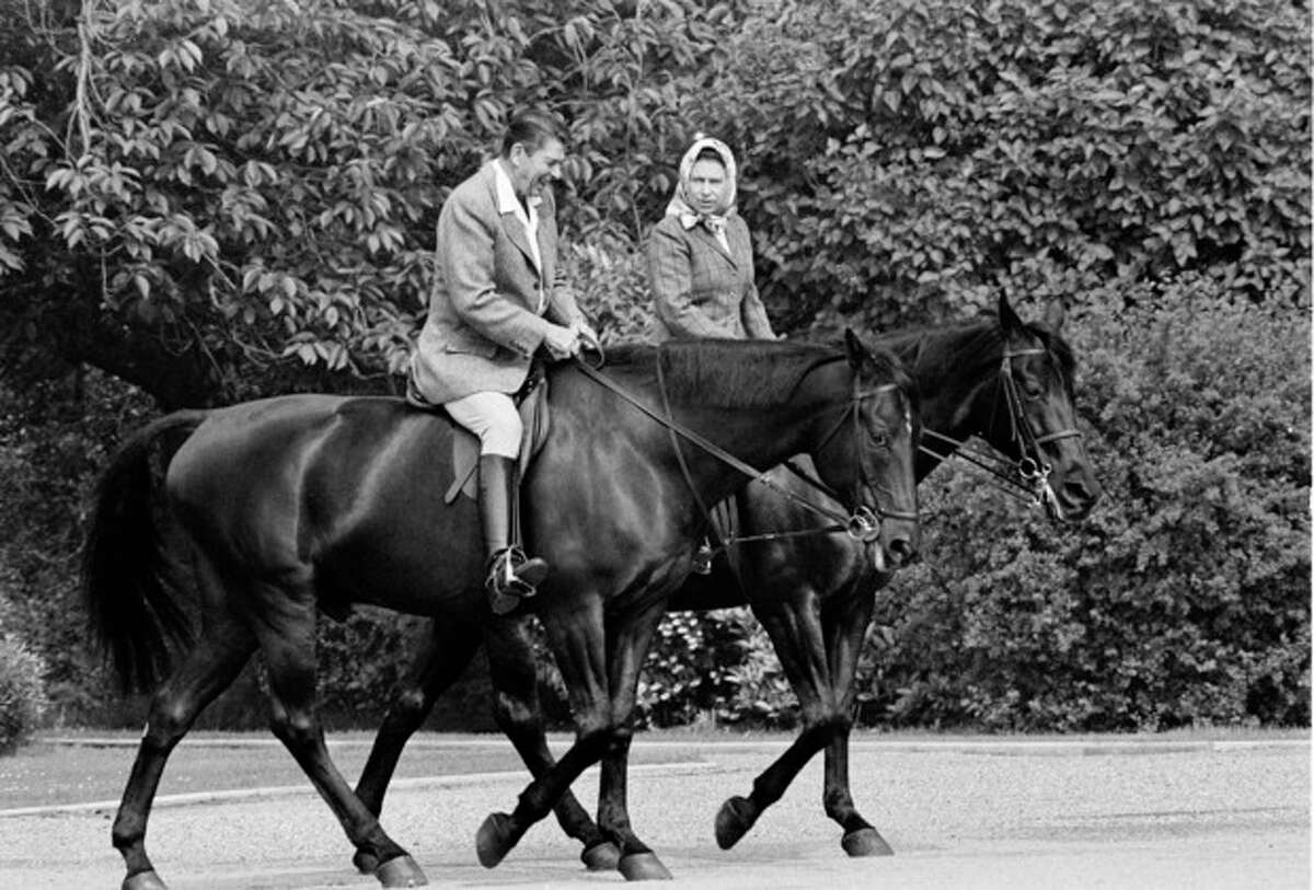 FILE - In this June 8, 1982 file photo, U.S. President Ronald Reagan, on Centennial, and Britain's Queen Elizabeth II, on Burmese, go horseback riding on the grounds of Windsor Castle, England. It is not often that the president of the United States needs to seek fashion advice. But when Ronald Reagan was getting ready for a visit to England as a guest of Queen Elizabeth II in June 1982, his people had an important question for the Brits: Just what does one wear to go riding with the queen in the magnificent horse country surrounding Windsor Castle? The answer: Something smart, but casual, of course. Riding boots, breeches and a turtleneck sweater would do fine _ no need for formal riding attire. The fashion inquiry is but one tidbit contained in nearly 500 pages of formerly Confidential documents relating to the Reagan visit being made public Friday, Dec. 28, 2012 by Britain?'s National Archives. (AP Photo/Bob Daugherty, File)