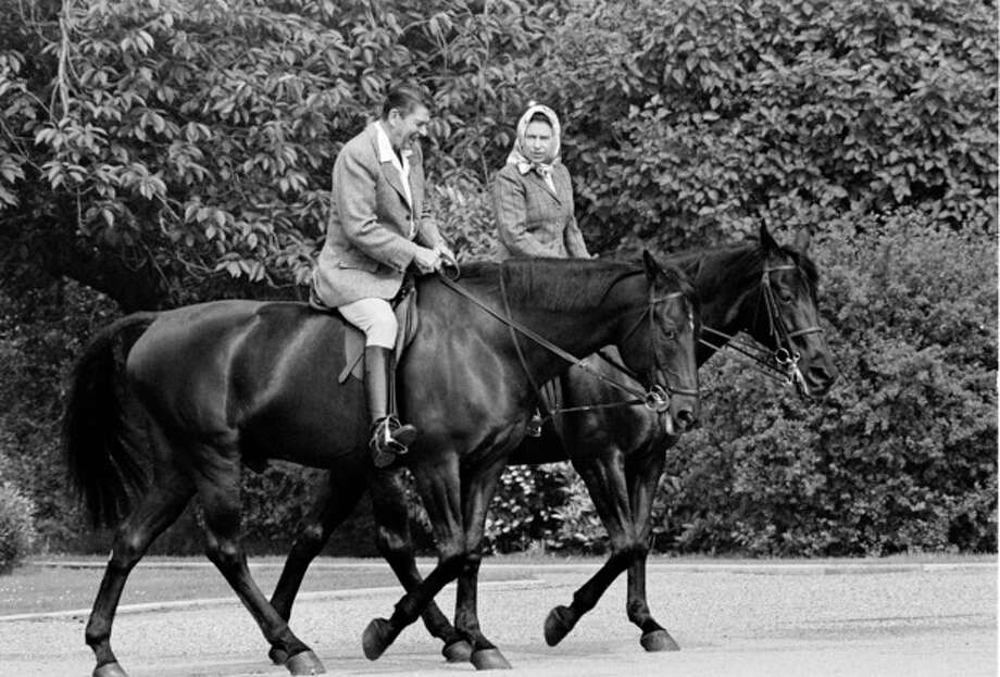 FILE - In this June 8, 1982 file photo, U.S. President Ronald Reagan, on Centennial, and Britain's Queen Elizabeth II, on Burmese, go horseback riding on the grounds of Windsor Castle, England. It is not often that the president of the United States needs to seek fashion advice. But when Ronald Reagan was getting ready for a visit to England as a guest of Queen Elizabeth II in June 1982, his people had an important question for the Brits: Just what does one wear to go riding with the queen in the magnificent horse country surrounding Windsor Castle? The answer: Something smart, but casual, of course. Riding boots, breeches and a turtleneck sweater would do fine _ no need for formal riding attire. The fashion inquiry is but one tidbit contained in nearly 500 pages of formerly Confidential documents relating to the Reagan visit being made public Friday, Dec. 28, 2012 by Britain's National Archives. (AP Photo/Bob Daugherty, File) / AP