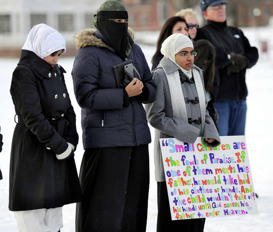 From left, Naveera Karim, Ayesha Akhtar and Anwar Abdulrehman, members of the Islamic Society of Western Connecticut, attend an interfaith prayer vigil to remember the victims of the Sandy Hook elementary school shootings Friday, Dec. 28, 2012 in Newtown, Conn. Friday morning marked two weeks since a gunman killed 20 children and six educators at the Sandy Hook Elementary School. (AP Photo/Danbury News-Times, Carol Kaliff) / Danbury News-Times