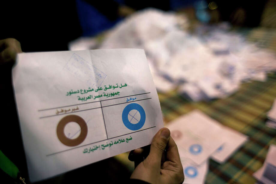 An Egyptian election worker eliminates an invalid ballot while counting ballots at the end of the second round of voting on a referendum on a disputed constitution drafted by Islamist supporters of President Mohammed Morsi at a polling station in Giza, Egypt, Saturday, Dec. 22, 2012. Egypt's Islamist-backed constitution headed toward likely approval in a final round of voting on Saturday, but the deep divisions it has opened up threaten to fuel continued turmoil. (AP Photo/Nasser Nasser) / AP