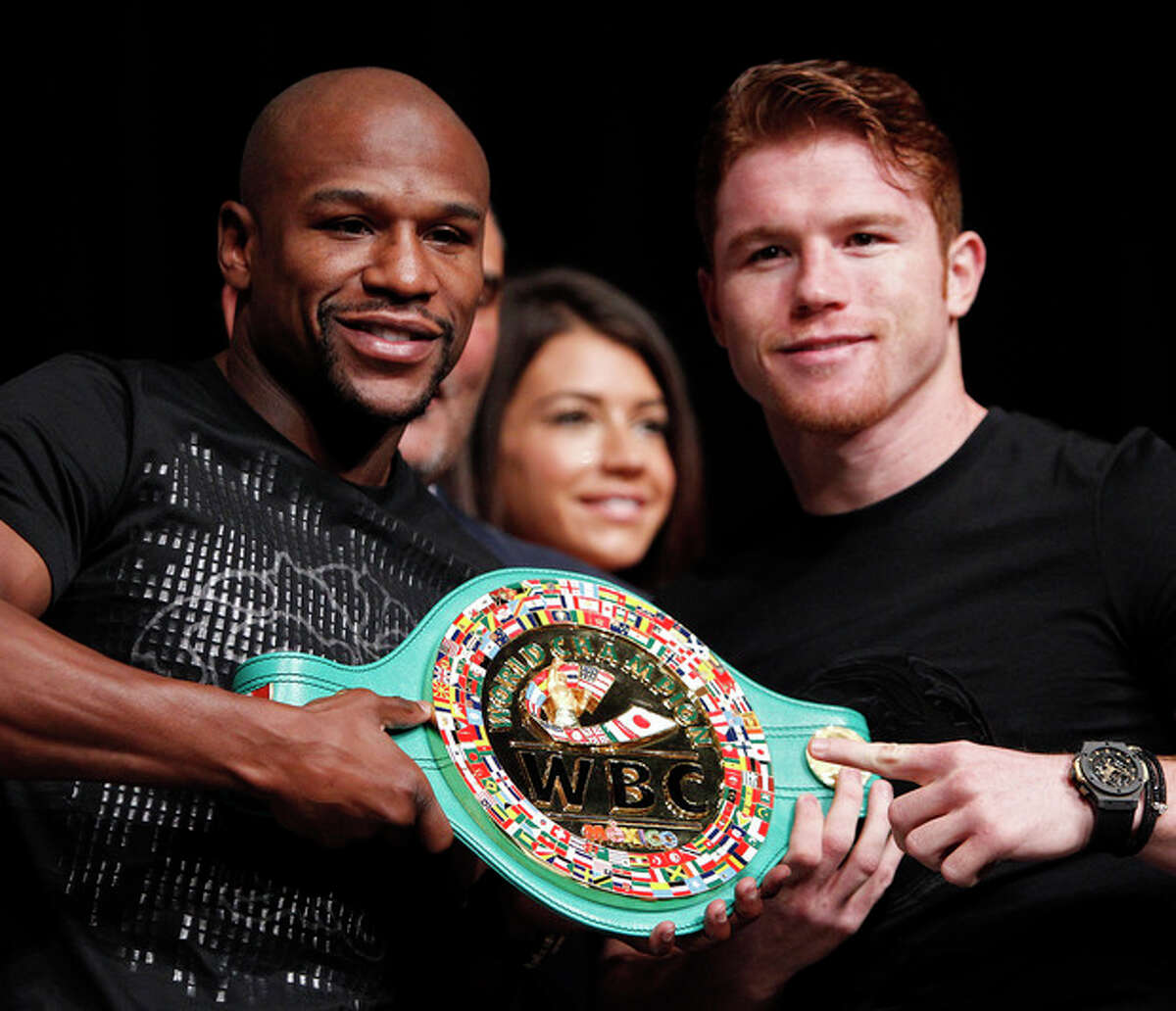 Boxers Floyd Mayweather, left, and Canelo Alvarez pose during a press conference in Las Vegas, Wednesday, Sept. 11, 2013. The pair are scheduled to fight on Saturday for Mayweather's WBA Super World and Alvarez's WBC junior middleweight titles. (AP Photo/Las Vegas Review-Journal, John Locher) LOCAL TV OUT; LOCAL INTERNET OUT; LAS VEGAS SUN OUT