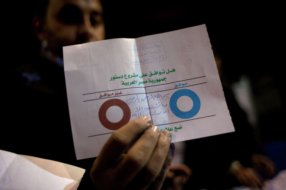 An Egyptian election worker shows his colleagues an invalid ballot while counting ballots at the end of the second round of a referendum on a disputed constitution drafted by Islamist supporters of president Mohammed Morsi at a polling station in Giza, Egypt, Saturday, Dec. 22, 2012. Egypt's Islamist-backed constitution headed toward likely approval in a final round of voting on Saturday, but the deep divisions it has opened up threaten to fuel continued turmoil. (AP Photo/Nasser Nasser) / AP