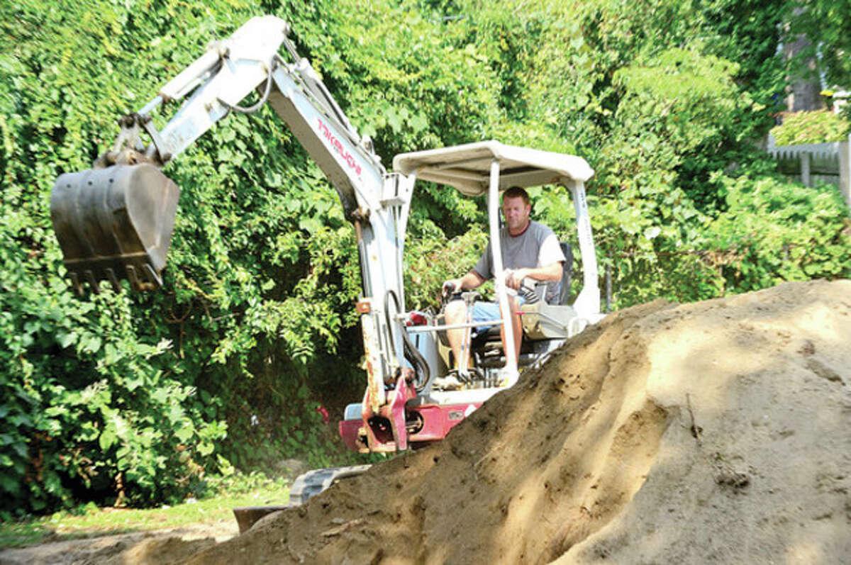 Matt Lee works on the construction of new Bouton Street Park playground Thursday. Hour photo / Erik Trautmann