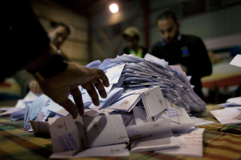 Egyptian election workers count ballots at the end of the second round of a referendum on a disputed constitution drafted by Islamist supporters of president Mohammed Morsi at a polling station in Giza, Egypt, Saturday, Dec. 22, 2012. Egypt's Islamist-backed constitution headed toward likely approval in a final round of voting on Saturday, but the deep divisions it has opened up threaten to fuel continued turmoil. (AP Photo/Nasser Nasser) / AP