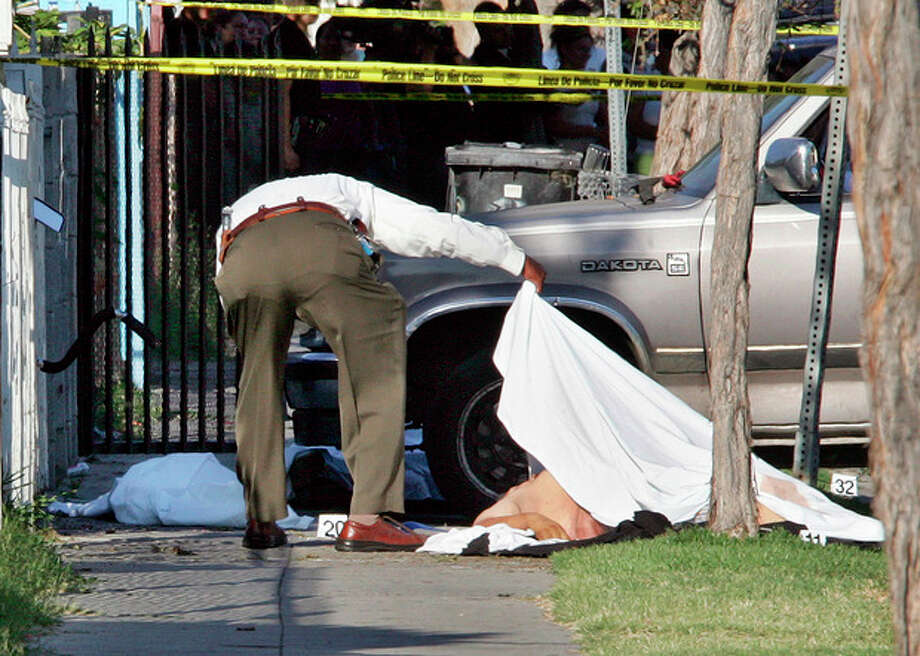 FILE - In this June 30, 2006 file photo, an investigator views one of three gunshot victims on 49th Street in South Los Angeles. A gunman toting an assault rifle got out of a vehicle and shot to death 10-year-old David Marcial, the boy's 22-year-old uncle and a 17-year-old neighbor. David's 12-year-old brother, Sergio, survived. In the wake of the Dec. 14, 2012 mass shooting at Sandy Hook Elementary School in the small town of Newtown, Conn., there is now much political discussion about gun control. For urban advocates, this new emphasis on gun control is long overdue. (AP Photo/Reed Saxon, File) / AP