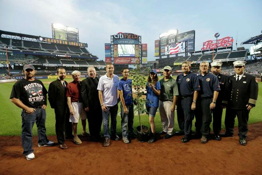 "Prescott, Ariz., Wildland Division chief Darrell Eugene Willis, fourth from right, and Public Information officer Wade Michael Ward, third from right, pose with other recipients of the ""9/11 Memorial Survival Tree Program"" before a baseball game between the New York Mets and the Washington Nationals, Wednesday, Sept. 11, 2013, in New York. (AP Photo/Frank Franklin II) / AP"