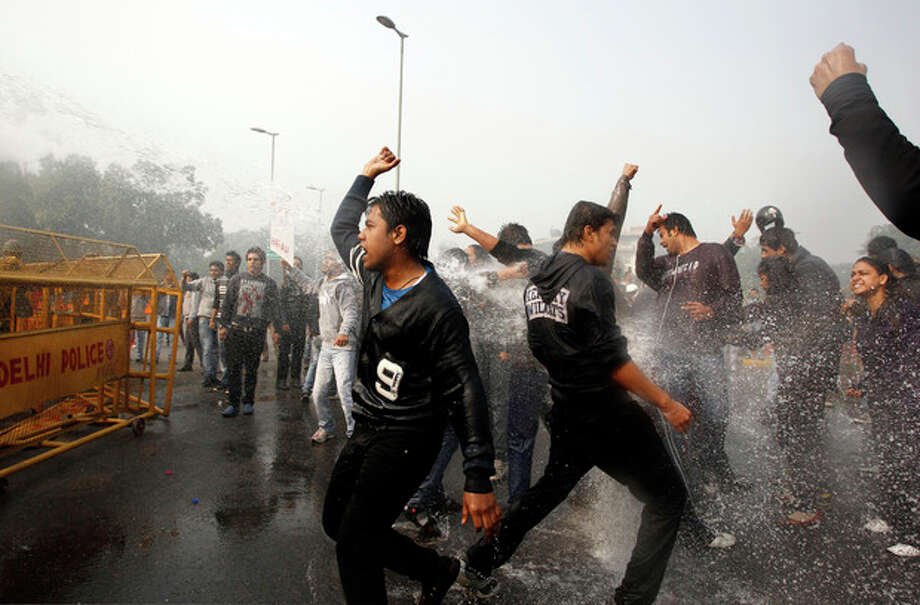 Indian protesters shout slogans as policemen use water cannon to disperse those demonstrating against a gang rape and brutal beating of a 23-year-old student on a bus, in New Delhi, India, Sunday, Dec. 23, 2012. The attack last Sunday has sparked days of protests across the country. (AP Photo/Tsering Topgyal) / AP