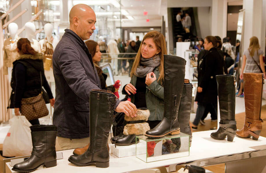 In this photo of Friday, Oct. 12, 2012, customers shop for Rudsak shoes at Macy's shoe department in New York. Shoes are coming out of the closet and landing under the Christmas tree. They're a top seller this holiday season _ a big feat considering they don't usually make peoples' gift lists. (AP Photo/Mark Lennihan) / AP