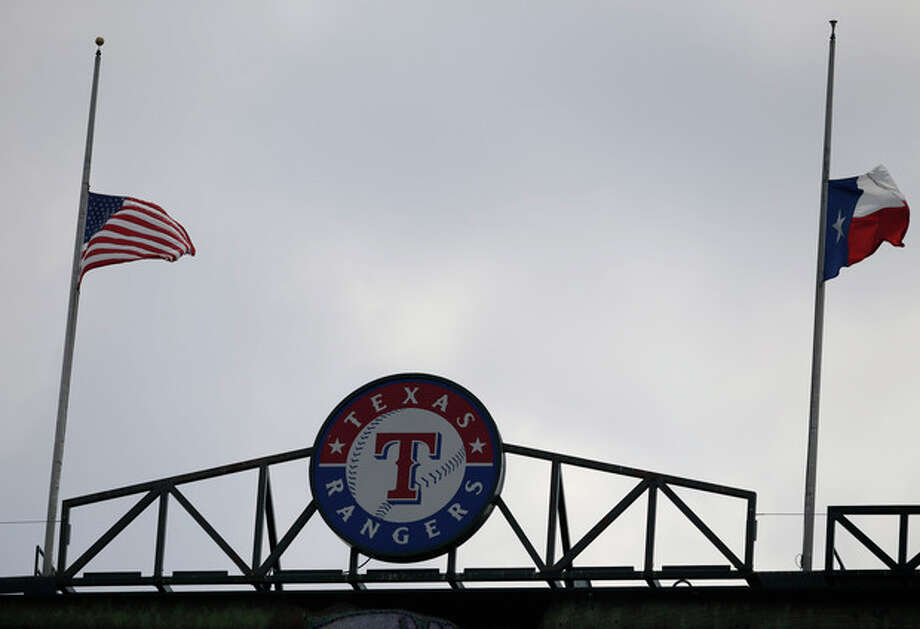 The United States, left, and Texas flags wave in the breeze at half staff, in honor of the 12th anniversary of the Sept. 11 terrorist attacks, during the first inning of a baseball game betwen the Pittsburgh Pirates and Texas Rangers Wednesday, Sept. 11, 2013, in Arlington, Texas. (AP Photo/Tony Gutierrez) / AP