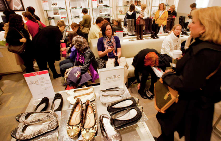 In this photo of Friday, Oct. 12, 2012, customers shop at Macy's shoe department in New York. Shoes are coming out of the closet and landing under the Christmas tree. They're a top seller this holiday season _ a big feat considering they don't usually make peoples' gift lists. (AP Photo/Mark Lennihan) / AP