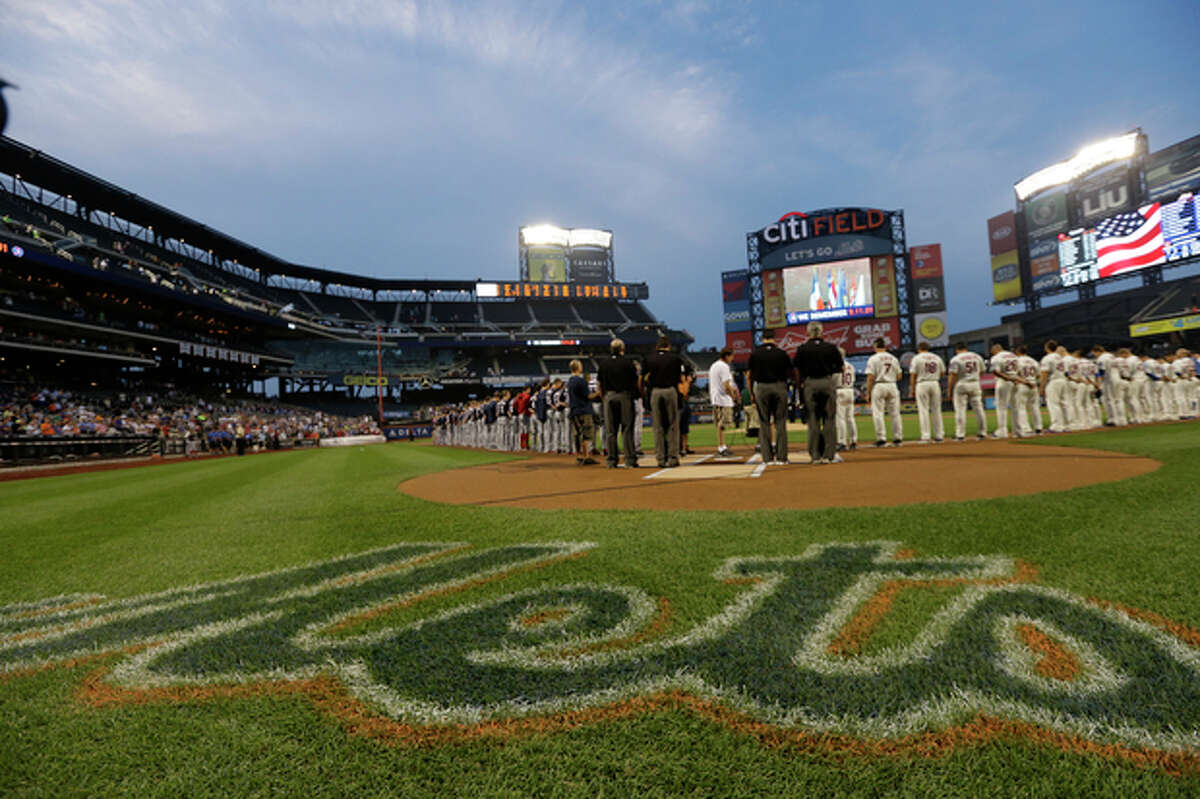 The Washington Nationals and the New York Mets line up on the field during the singing of the national anthem before a baseball game on Wednesday, Sept. 11, 2013, in New York. (AP Photo/Frank Franklin II)