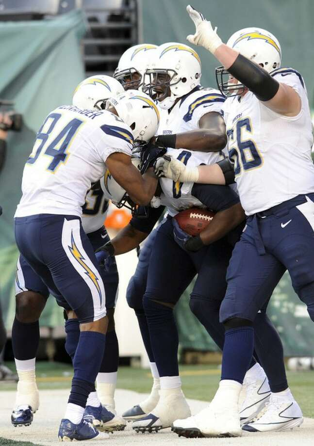 San Diego Chargers tight end Antonio Gates (holding ball), center, celebrates with teammates after scoring a touchdown against the New York Jets during the second half of an NFL football game on Sunday, Dec. 23, 2012, in East Rutherford, N.J. (AP Photo/Bill Kostroun)