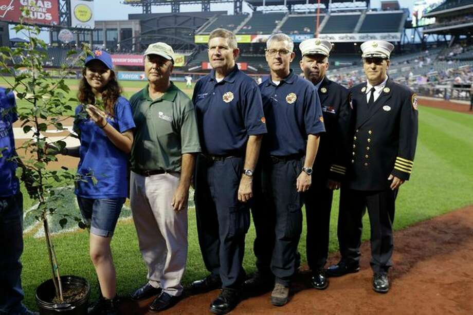 "Prescott, Ariz., Wildland Division chief Darrell Eugene Willis, fourth from right, and Public Information officer, Wade Michael Ward, third from right, pose with other recipients of the ""9/11 Memorial Survival Tree Program"" before a baseball game between the New York Mets and the Washington Nationals, Wednesday, Sept. 11, 2013, in New York. (AP Photo/Frank Franklin II) / AP"