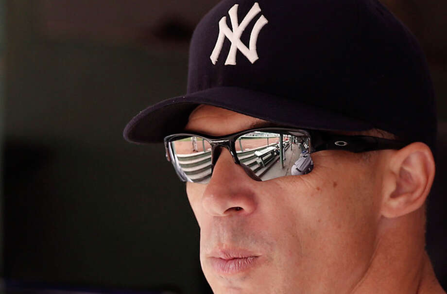 New York Yankees manager Joe Girardi looks on from the dugout before their baseball game against the Boston Red Sox at Fenway Park in Boston Saturday, Sept. 14, 2013. (AP Photo/Winslow Townson) / FR170221 AP